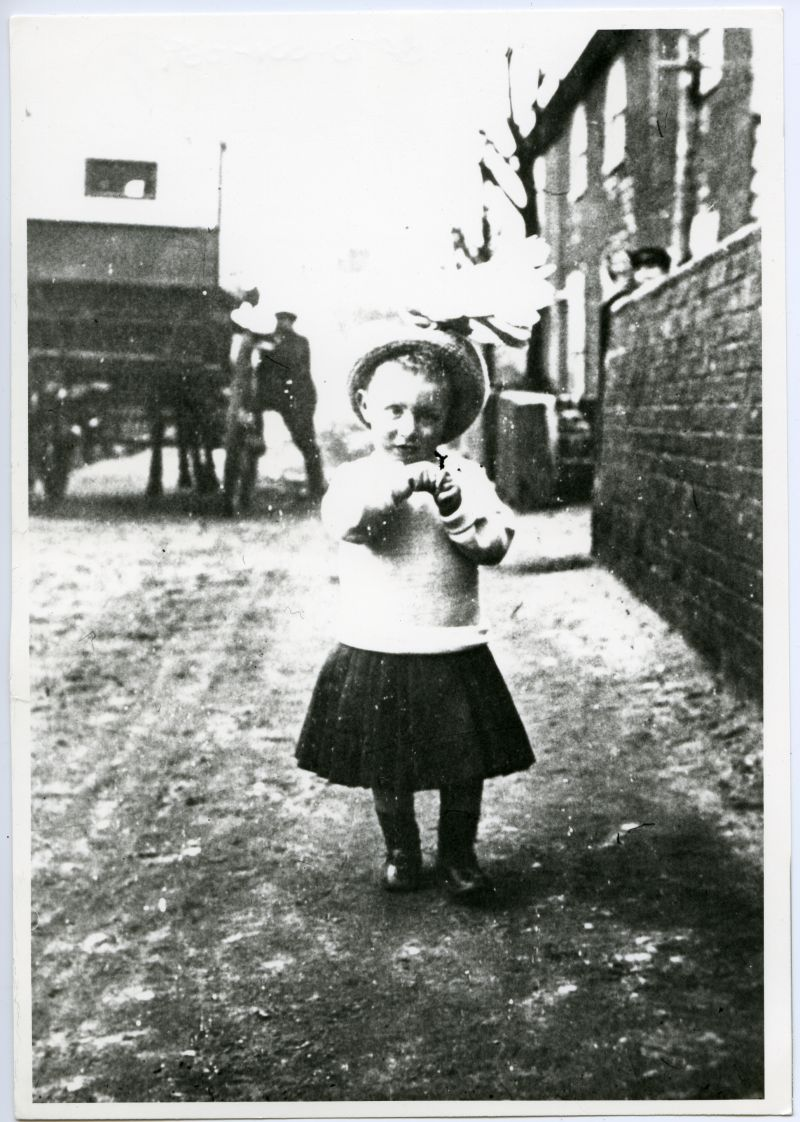 Unknown child standing in street with horse and cart in background 
