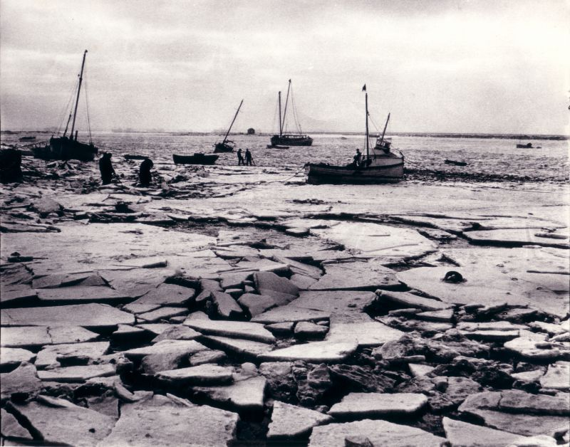 The severe winter 1962-63 at West Mersea Hard looking out towards the Packing Shed and the river. Wherever possible boats were brought ashore and any wooden boats left in the creeks suffered in the ice. 