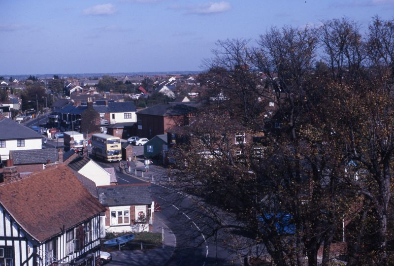 View from West Mersea church tower. White Hart on left. High Street. Bus waiting outside MICA. 