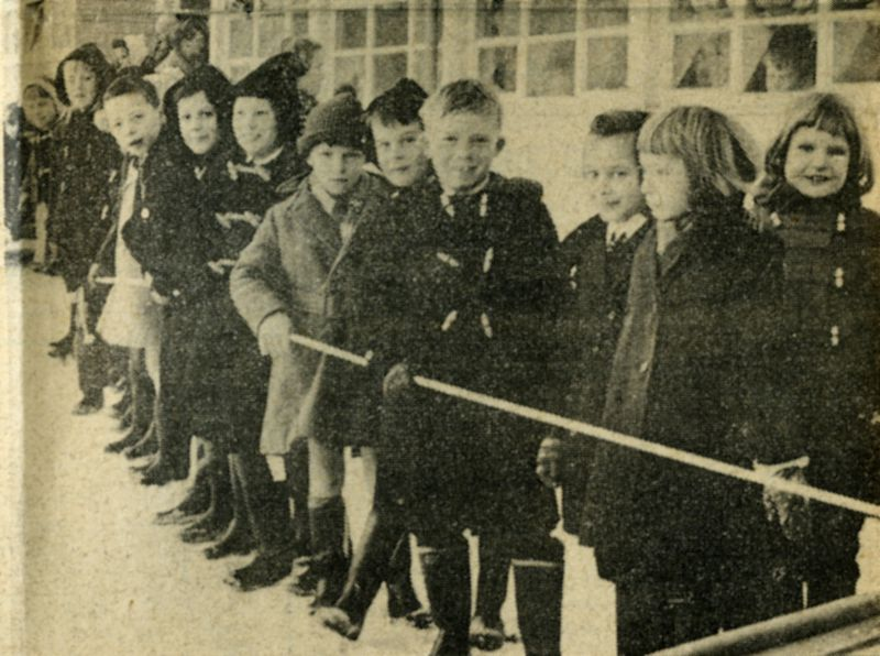 Children from West Mersea watching the helicopter which landed in the school grounds to collect supplies for the ships cut off in the River Blackwater.