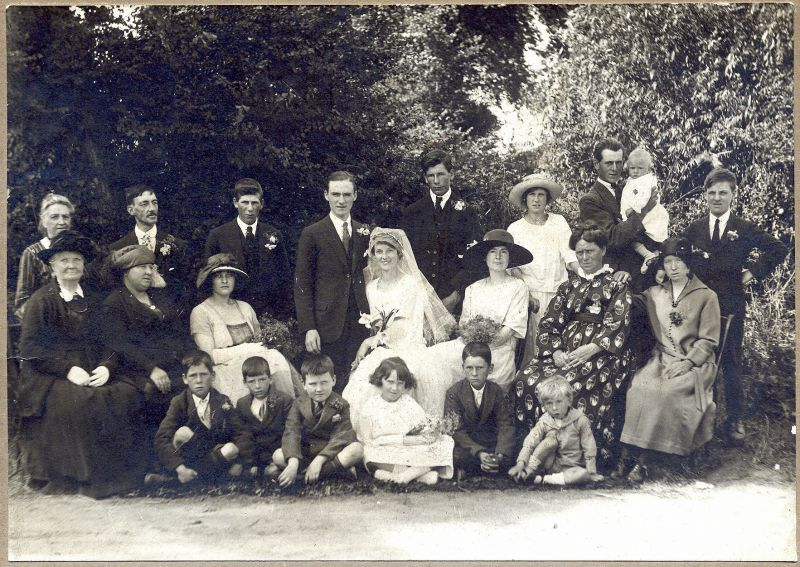 A Johnson family wedding. This took place on 6 August 1923 when George Lyall from London married Alice Frances Emma Johnson of Haycocks Farm. Bertie Johnson stands behind the bride, on her left. The bride's mother, Mrs. Alice Johnson, sits next but one on her left. Sitting on the ground at the right of the row of children is Harold Johnson and on his right is his brother Stanley.