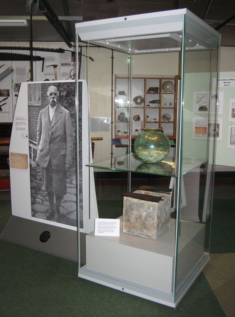 2012 Summer Exhibition. Samuel Hazzledine Warren. Display cabinet with contents of the tomb from Mersea Barrow - the glass urn containing cremated bones, and underneath it, the lead box. 