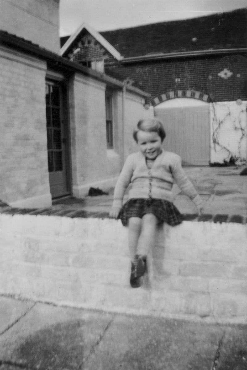 Anthea Harding sitting on the wall at her grandparent's house - 'Strood Close' on the Peldon side of the Strood. This wall came down in the 1953 flood. 