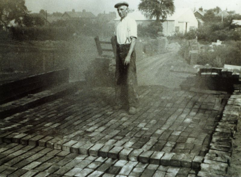 Brickmaker Bill Gasson about to unload the kiln. Mersea brickyard - Underwoods Garage in background. 