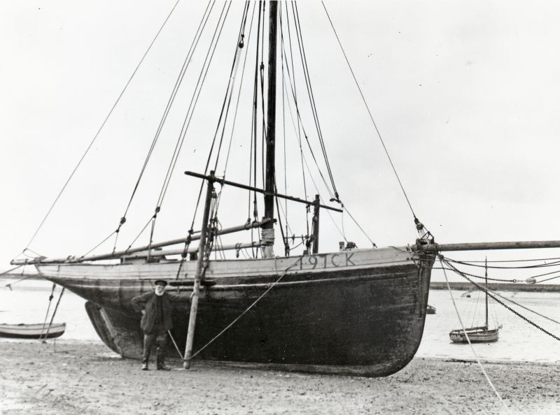 William Wyatt, the West Mersea boatbuilder, stands against the legged up West Mersea smack UNITY 197CK. The UNITY was perhaps the fastest of the West Mersea smacks of her time. She ended as a hulk on Foulness Island in the 1940s. 