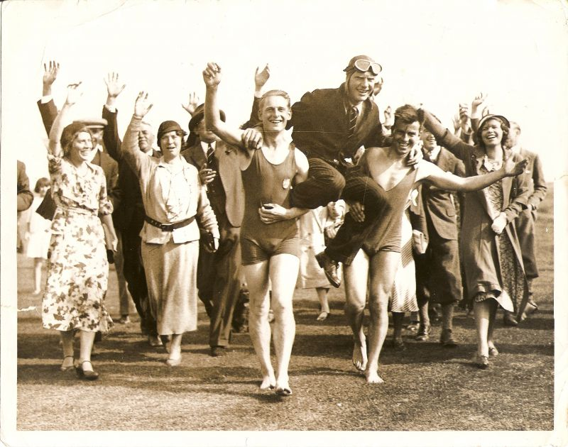 Mr Charles Scott lands on the Golf Course near the sea and is carried by two bathers, followed by local folk. Mrs Scott is on the right (wearing a coat). The bather on the left of the picture is Frank French. 