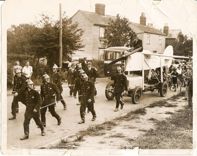 Mr Charles Scott's journey through the village, towed by firemen. C.W.A. Scott was an aviator who had flown to Australia. He was a Mersea resident. Picture was taken on Colchester Road, Mersea. There is an Underwood's bus in the background. 