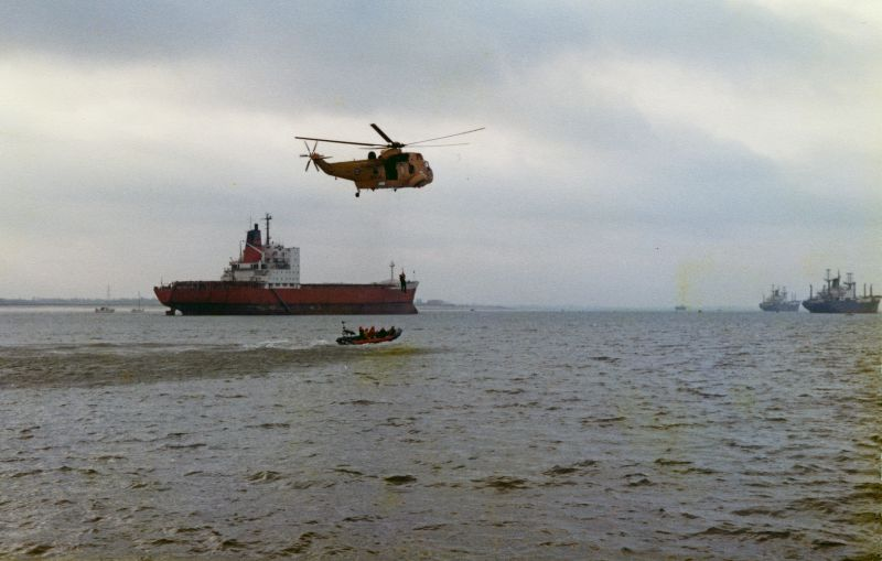 West Mersea Lifeboat exercise with RAF Sea King helicopter in the River Blackwater. In the background are left laid up container ship MANCHESTER VANGUARD and on the right FLAMAR PROGRESS and FLAMAR PRIDE. Date: cJanuary 1982.