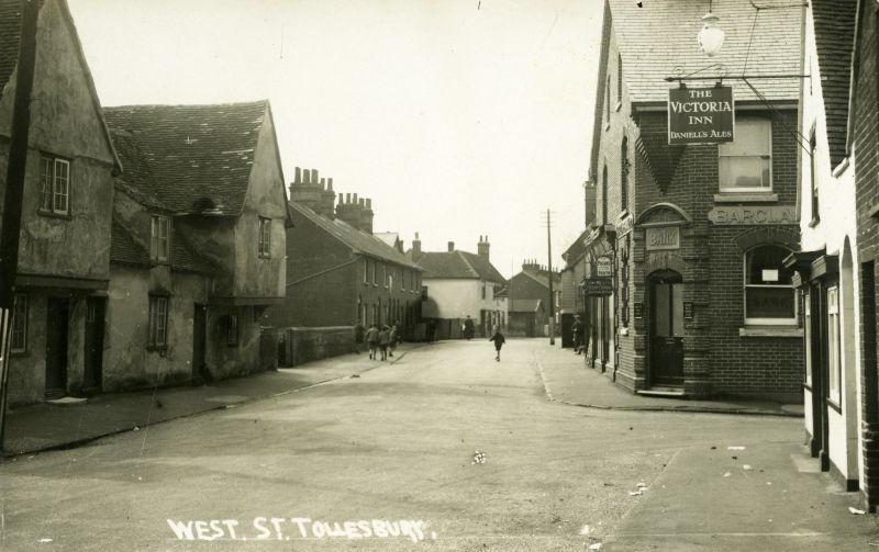 West Street, Tollesbury. Postcard. Barclay's Bank on corner of North Road. Victoria Inn - Daniell's Ales - on the right. 