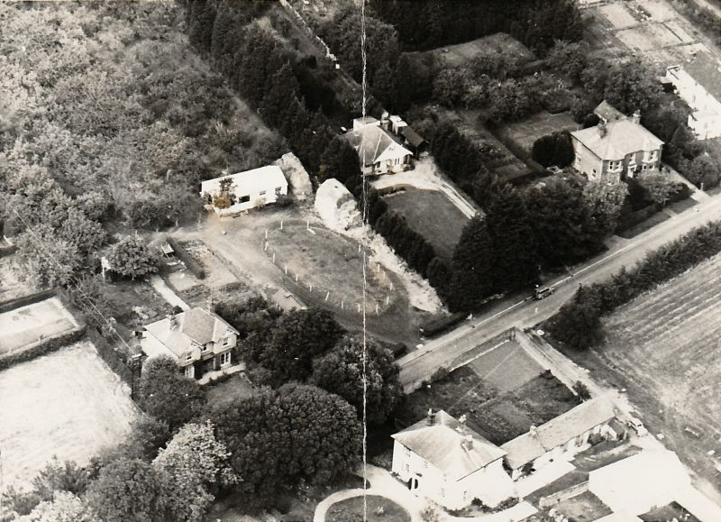 Aerial view of part of East Road, West Mersea, looking northeast. Brierley Hall is lower centre. On the left is Mondamin, with Patricia Catchpole's stables next door. To the east of the stables is the bungalow Torbay and then the large house upper right was the Maples, owned by the Kemp family, and now demolished. 