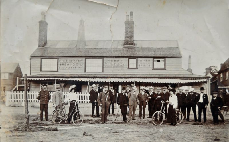 A party outside the Victory Inn, perhaps in Mersea to enjoy the Oyster Teas advertised by the Victory. The writing on the front of the Inn says Colchester Brewing Co., Ales and Stout, Wines and Spirits. Proprietor W. Trim. 1894 Kelly's lists George Brand as the licensee, so Bill Trim must have taken over after that. The latest date it would be is around 1907 when the license transferred to the ...