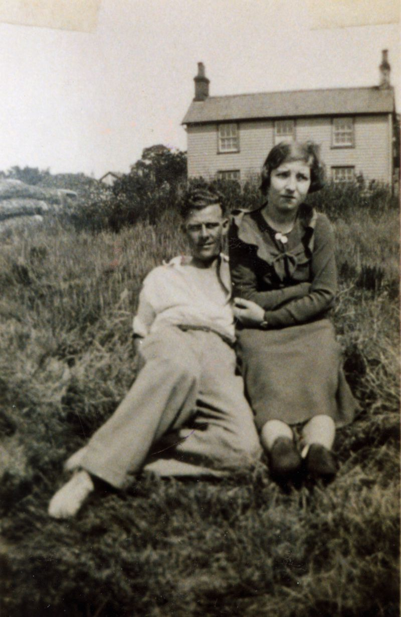 Joe Hewes with girl friend taken along Coast Road. Munson Cooke's cottage in background.