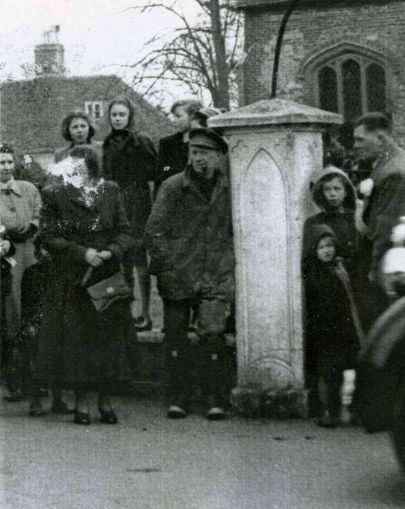 West Mersea church gate. Chum Hewes leaning against the pillar. Silvia D'Wit near the right.