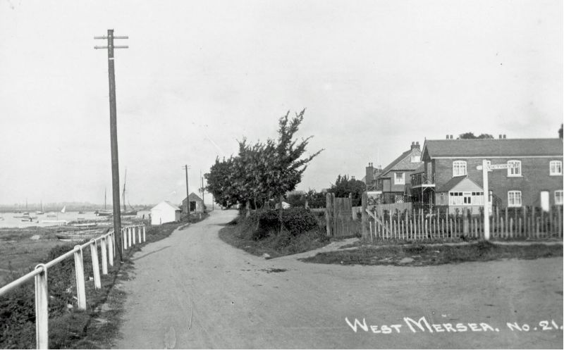 Coast Road and the corner of Victory Road. The first house on the right is Cathay. Boomie barge BRITANNIC and Hempstead's shed in the distance. Postcard West Mersea No.21.