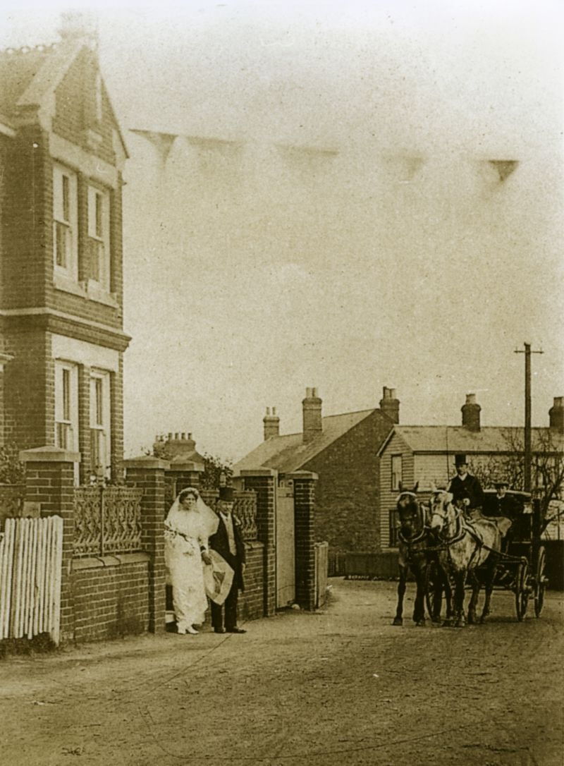 Off to Church. Outside Roosevelt (now 87 East Street) at the top of Woodrolfe Road, a bride waits to board the carriage pulled by two fine horses to take her to be married. From the house, flags are flying across the road, a custom which was frequently observed in the village when there was a wedding.