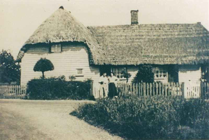 Thatched Cottages (now called Stable Fields) at Hardy's Green, Birch. 1930s. Possibly Jean and Bernard Pepper standing in road.