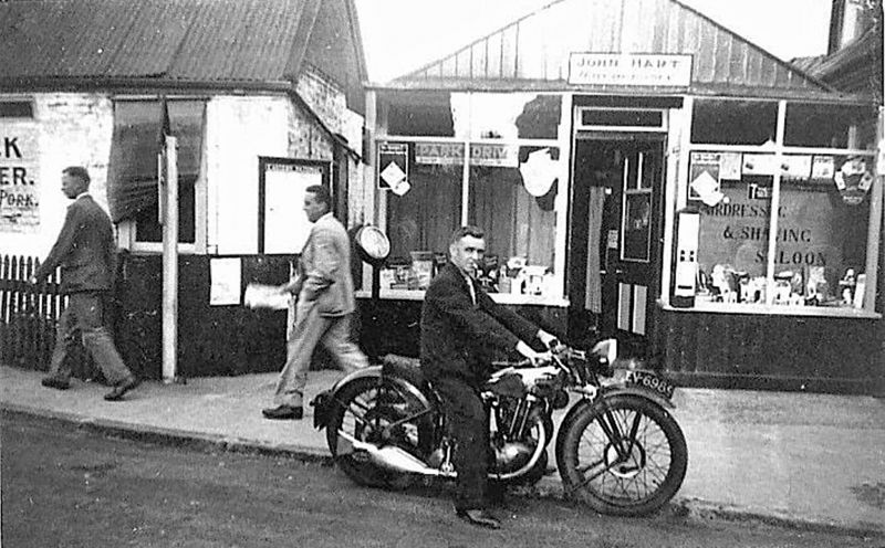 Bert Hempstead on motorcycle EV6989. Johnny Hart's Hairdressing in High Street, behind Arthur Cock's butchers.