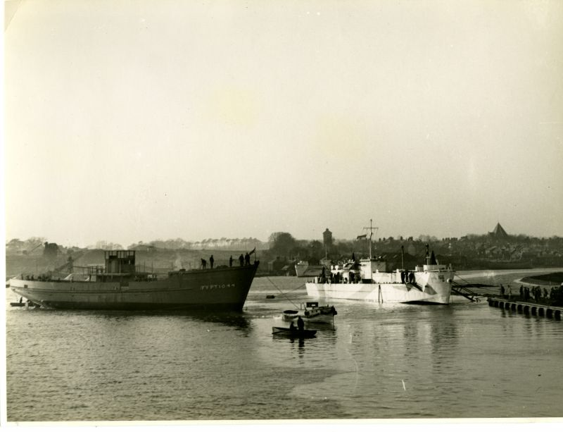 A quiet interlude during war. Wooden motor minesweeper FY PT 1044 is towed to the fitting out berth after launch from Wivenhoe Shipyard Ltd., in 1943. The river Colne brims at mid-day high water and the ship floats high without her engines, equipment, fuel, water and stores. A motor launch tows her in towards hands waiting to moor her at the Railway Quay (right).