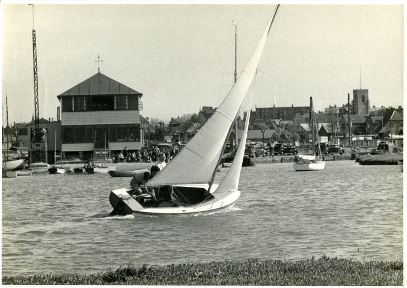 2. ID BOXB5_015_003 A new Jewel-class 14-footer finishes in front of the Walton and Frinton Yacht Club in 1952. Walton has two aspects; its Victorian front faces the North Sea, but ...