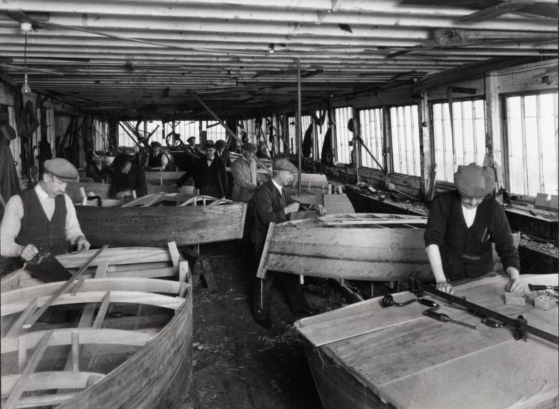 Husk's boatyard, Wivenhoe, about 1930. From right: John Smith, Stanley Cook (foreman), extreme left James Theobald. The small boats under construction are for the boating lake at West Mersea.
