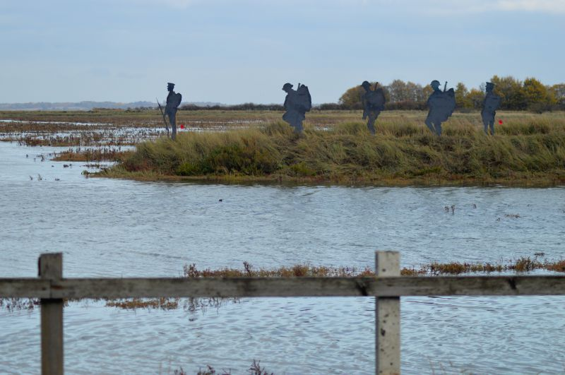East Mersea men atop the old sea wall looking to the mainland.