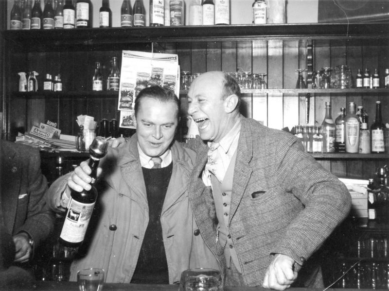 Geof Hempstead holding bottle with Herbert Bishop. Dog & Pheasant. 