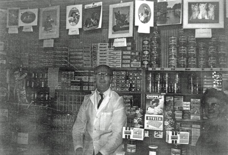 Peldon Shop - Leslie Mallett behind the counter. Who is the lady in the shadows on the right ? 