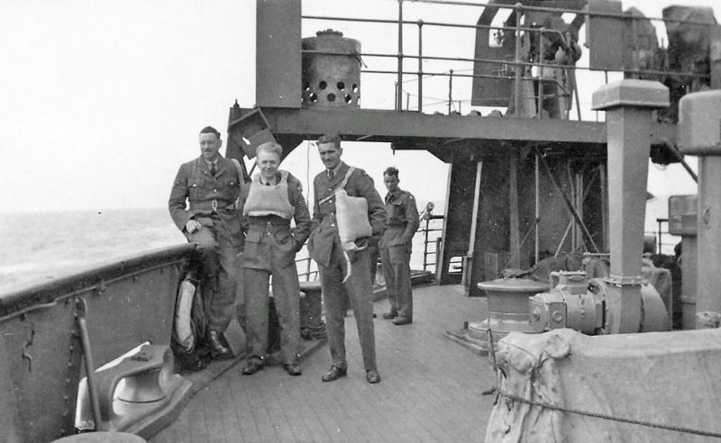 George Sanders Smith returning from Iceland. He is on the left, sitting on the rail. 