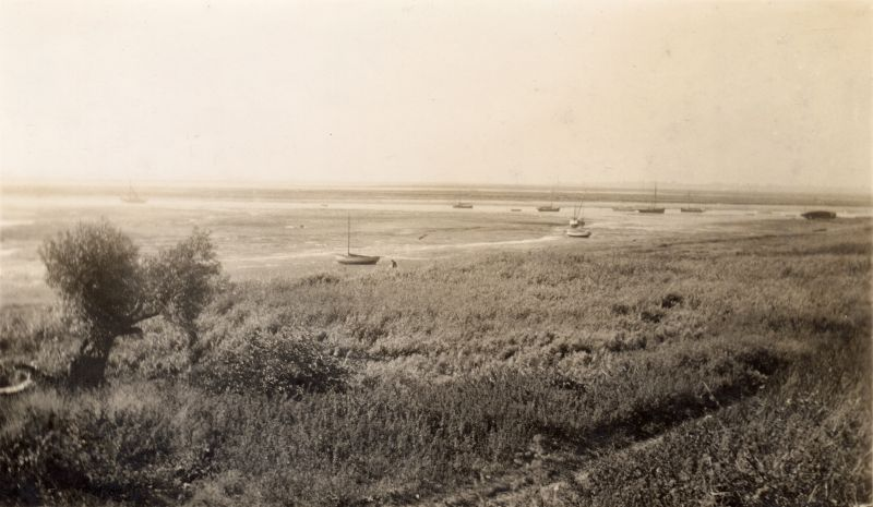 View by Monkey Steps on Coast Road looking across cricket field to Buzzen and Cobmarsh. The back of the photograph says 'Mersea from the city. 