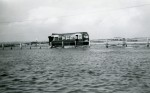 23. ID DBO_013 Eastern National bus going through the water at the Strood, in the days when bus services were not curtailed by the high tide. Ford Anglia Estate behind it ?