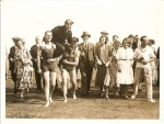 11. ID BS01_033 Mr Charles Scott being carried by two bathers after landing at the Golf Course. Barbara Mears is on the left with Bob Munro next to her. Charles Scott's first ...