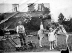 Mowing the grass at Shameen, Seaview Avenue. Ron Green's maternal grandfather Roland ('Roly') and an unknown girl. The donkey has shoes on, to avoid damaging the lawn.